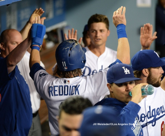 Josh Reddick is greeted with high-fives in the dugout after scoring in a run. Jill Weisleder/Dodgers