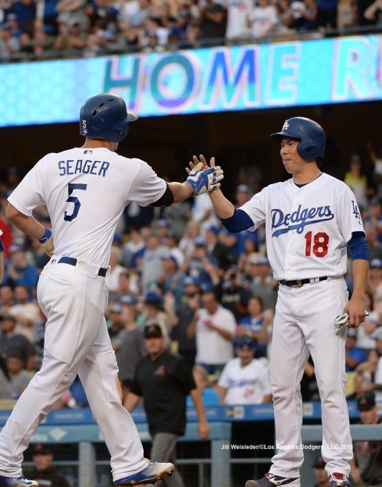 Kenta Maeda congratulates Corey Seager at home plate after getting a home run. Jill Weisleder/Dodgers