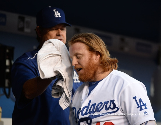 Pitching coach Rick Honeycutt wipes down Justin Turner in the dugout after coming in to score. Jill Weisleder/Dodgers