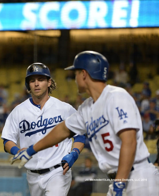 Corey Seager greets Josh Reddick after scoring in a run on a wild pitch. Jill Weisleder/Dodgers