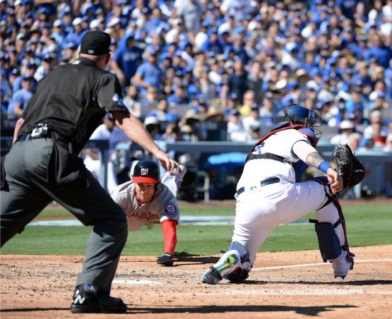 Tea Turner slides home safely under the glove of catcher Yasmani Grandal. Jill Weisleder/Dodgers